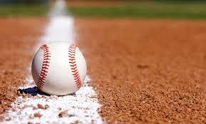 A baseball lies on the ground of a baseball field.